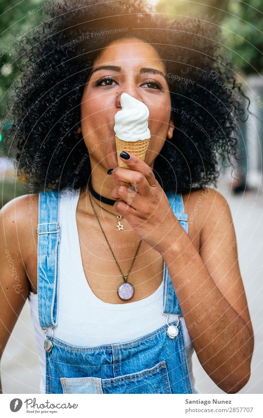 Portrait of a beautiful woman eating one ice cream. Woman Black African Afro Ice cream Cream Eating Lick Summer Hot Suck Human being Portrait photograph City