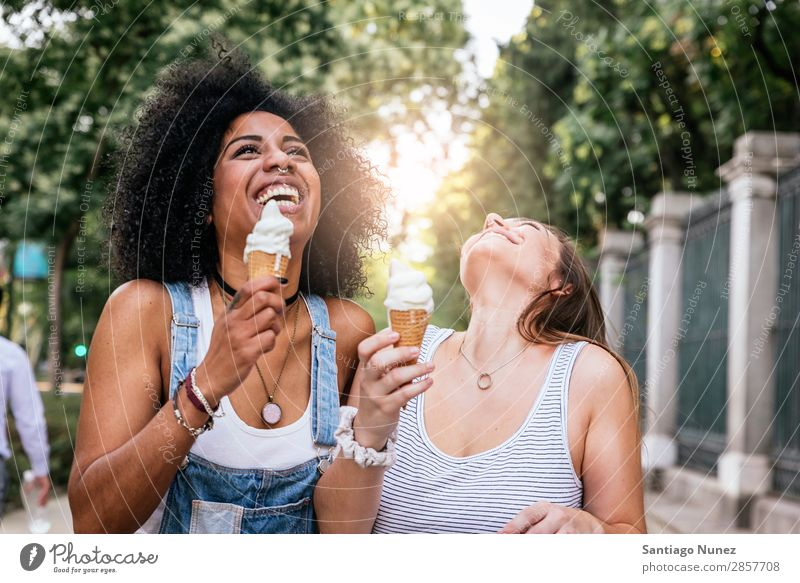 Beautiful women eating one ice cream in the street. Woman Friendship Youth (Young adults) Afro Ice cream cornet tasting Eating Cream Happy Summer