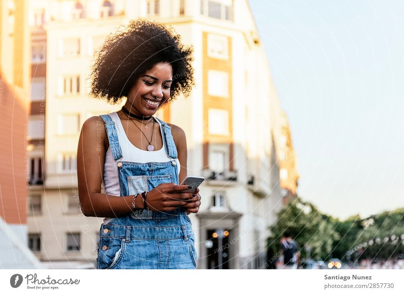 Beautiful woman using mobile in the Street. Woman Telephone Black African Mobile PDA texting Communication Afro Human being Portrait photograph City