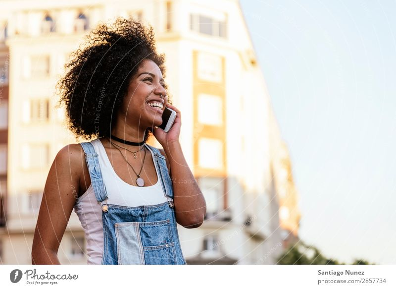 Beautiful woman using mobile in the Street. Woman Telephone Black African Mobile PDA speaking Afro Human being Portrait photograph City Youth (Young adults)