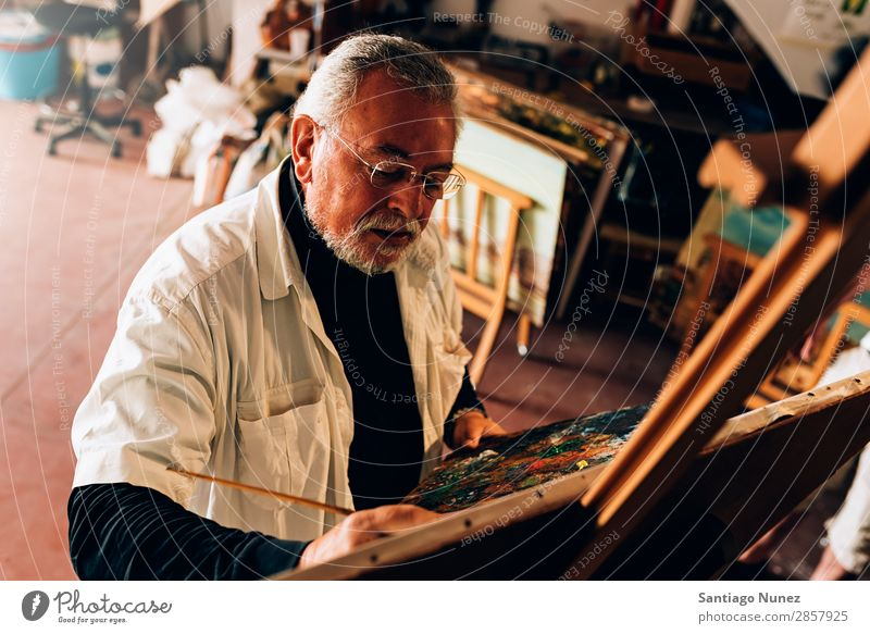 Old man artist painting oils in his studio. Man Adults Beard Artist Painter concentrated Painting and drawing (object) Paintbrush Brush Easel Canvas Concentrate