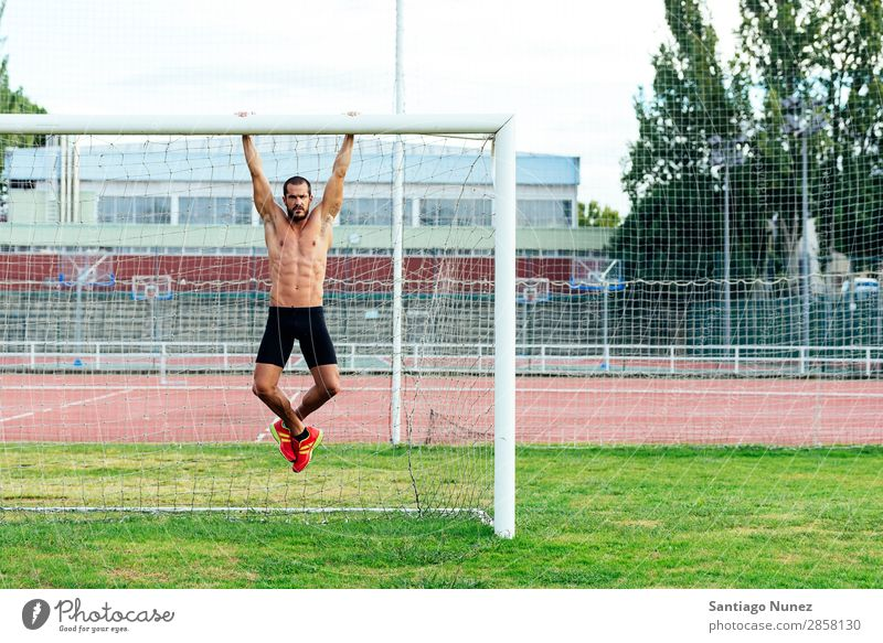 Man Doing Chin-ups outdoor. abs Action Athlete Attractive chin-up Practice Athletic Fitness goalpost Green Gymnasium handsome Healthy Horizontal instructor
