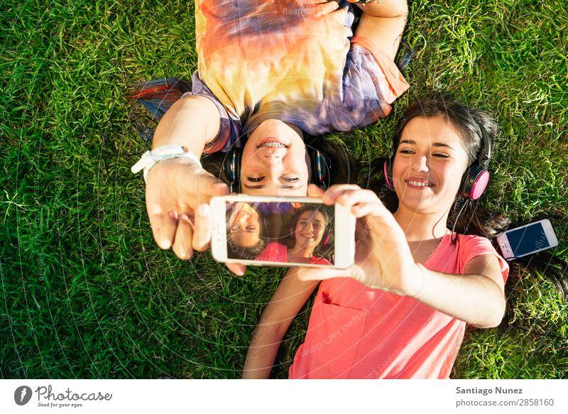 Two Teenage Girls Taking Selfie In Park American Attractive Beautiful braket Caucasian Solar cell Cellphone Woman Friendship Joy Grass Happy Headphones Laughter