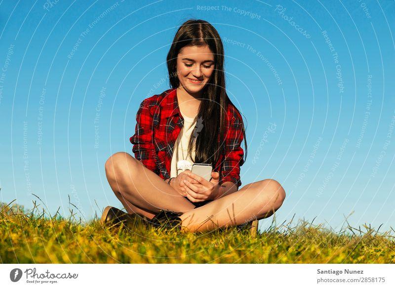 Happy Teenage Girl Using Mobile In Park American Attractive Beautiful braket Caucasian Solar cell Cellphone comunication Woman Friendship Joy Grass Headphones