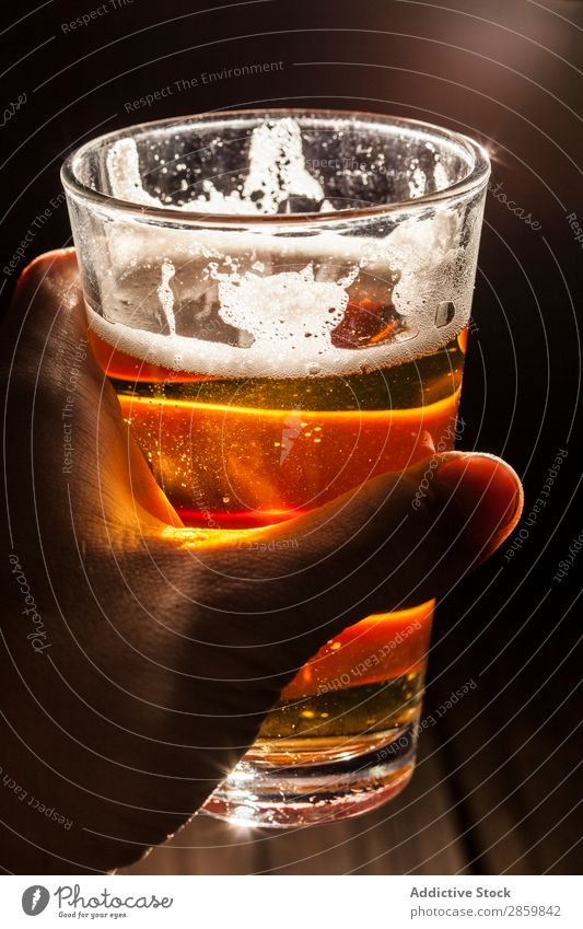 Man's hand holding a glass of berr with light at background Alcoholic drinks ale Bar Beer Beverage Bottle Brewery Cool (slang) Craft (trade) Drinking dry stout