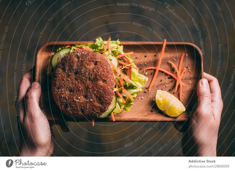 Woman holding a tray with a Vegetarian sandwich Avocado bio Bread Roll burger Carrot Cucumber Delicious Deluxe Diet eco Ecological Food Fresh Bird's-eye view