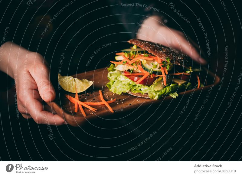 Woman holding a tray with a Vegetarian sandwich Avocado bio Bread Roll burger Carrot Cucumber Delicious Deluxe Diet eco Ecological Food Fresh Gourmet Hand