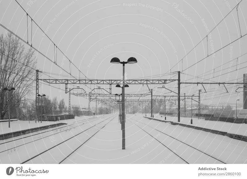 Railroad in snowy landscape Antique Cold Frost Frozen Industrial Exterior shot Platform Retro Snow snowing Station Train station Transport Vehicle Weather White