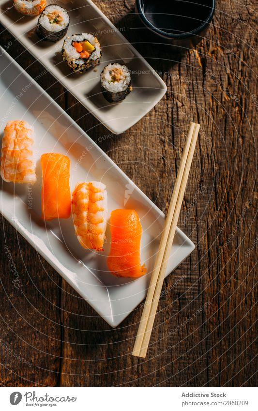 Sushi maki rolls and sashimi on a wooden background asian Avocado Chopstick Dish Fish Food Ginger Japanese nigiri nori Raw Rice Salmon Seafood soy sauce Table