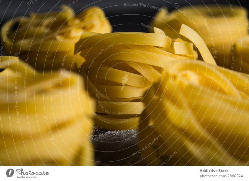 Raw tagliatelle on dark table Background picture Blackboard Board carbohydrate Close-up Dough Dry Egg Flour Food Fresh Healthy Home-made Italian Kitchen