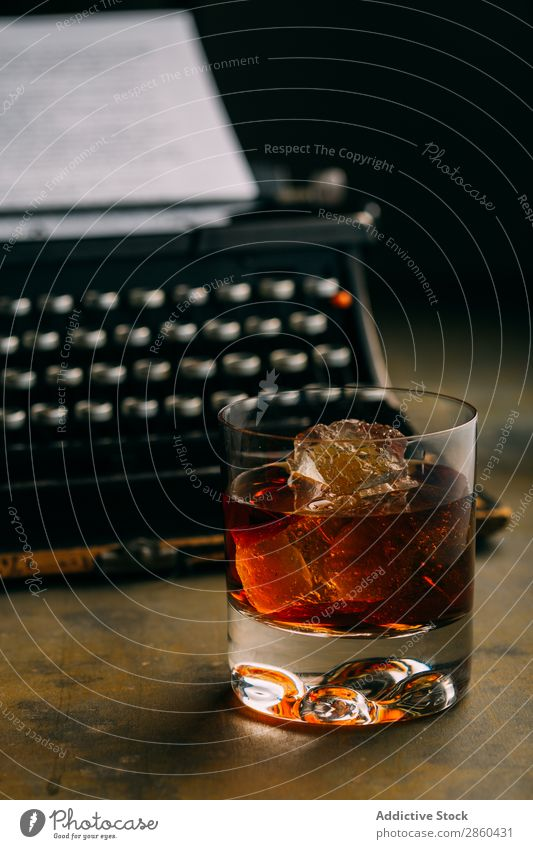 Glass of whiskey and a retro typewriter Alcoholic drinks Amber Analog Antique Beverage Bourbon Brandy Character Classic Cognac Creativity Drinking Gold Ice