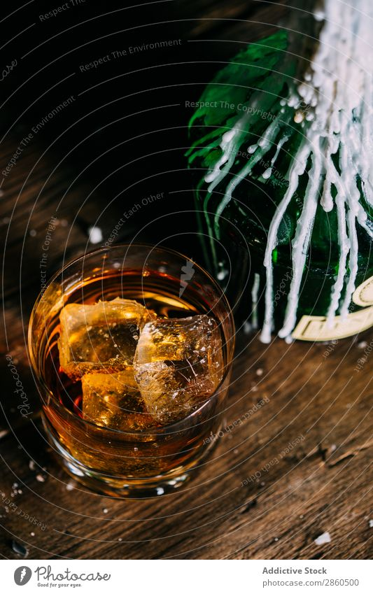 Glass of whiskey on a wooden table Alcoholic drinks Amber Background picture Bar barman bartender Beverage Bottle Bourbon Brandy Cognac Drinking Gold Hand Ice