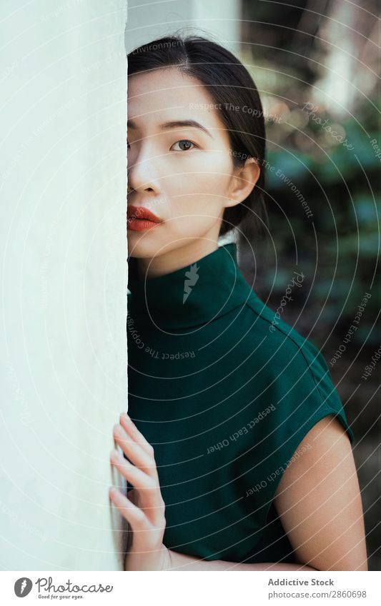 Asian woman leaning on wall Woman Youth (Young adults) Attractive Dress Green asian Japanese Wall (building) Lean Looking into the camera hiding Beautiful