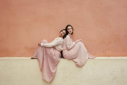 Women sitting together at orange wall Woman pretty Youth (Young adults) Beautiful Lean back to back Considerate Pensive Relationship lgtb Friendship Vintage
