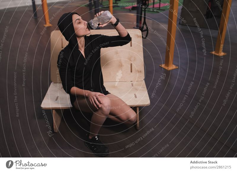 Smiling woman drinking with bottle of water in gym Woman Gymnasium Bottle Water Sportswear Bench Lady Cheerful Youth (Young adults) Thin Sit gymnastic Athletic