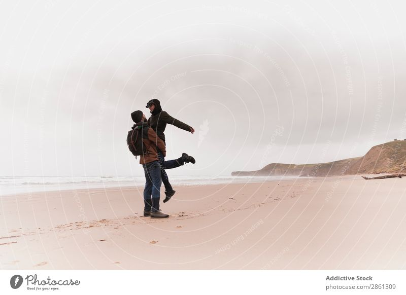 Couple kissing on sand shore near water Beach Kissing Water Sand Cold Coast Warmth Wear Backpack Hand Hold Man Woman Hat Ocean Hill Youth (Young adults) Love