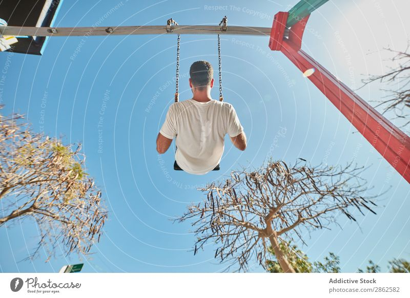 Man swinging on playground in sunlight swings Leisure and hobbies Town Playground Bright Sunlight Blue sky Contentment Street Action Expression Playing