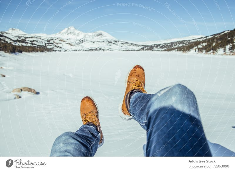 Man legs in winter boots on snow near mountains Boots Snow Winter Mountain cerdanya France Legs Jeans Beautiful weather Hill Sit Easygoing Warmth Comfortable