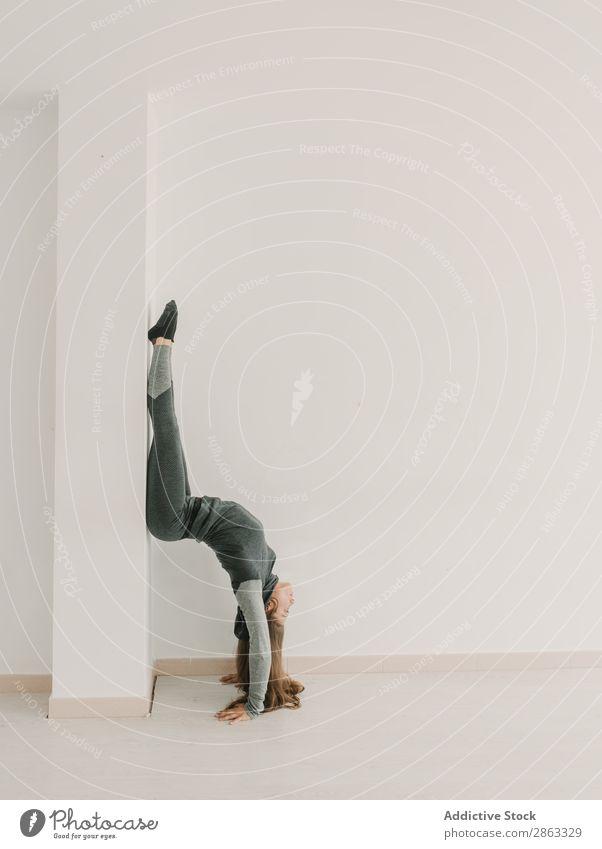 Flexible lady training upside down in studio Woman Handstand leg split Side Athletic Studio shot Light Room Fitness Practice Stretching Lady Sports Yoga pose