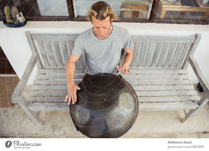 Blond man sitting on bench with big hand drum Man Drum handpan Bench Sit Hand Barefoot T-shirt Seat Blonde Window Door Building Music Guy instrument Playing