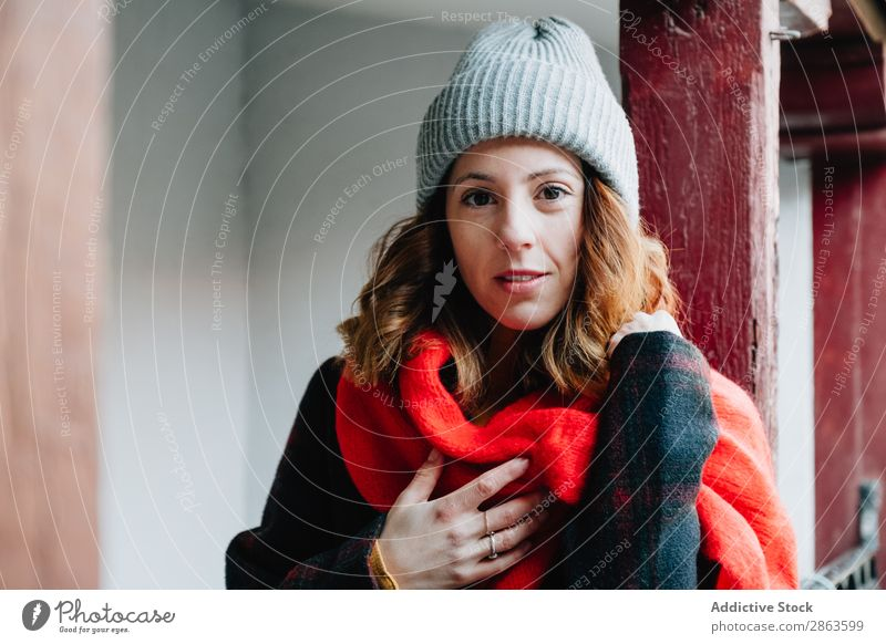 Positive woman in warm wear near house Woman Friendliness House (Residential Structure) Warmth Hand Chest Wear Winter Youth (Young adults) Building Lady