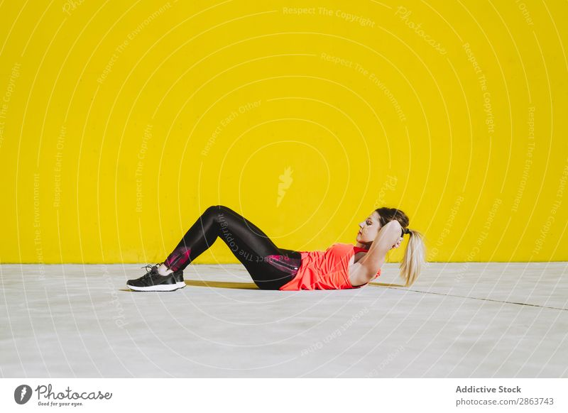 Woman doing sit ups exercises on floor Practice Sportswear Athletic Youth (Young adults) Story Fitness workout Wall (building) Press Yellow Lady Equipment Power