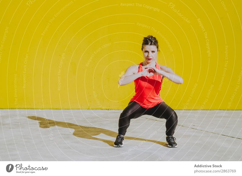 Woman doing squads exercises near a yellow wall Squad Practice Sportswear Athletic Youth (Young adults) Fitness workout Wall (building) Press Yellow Lady
