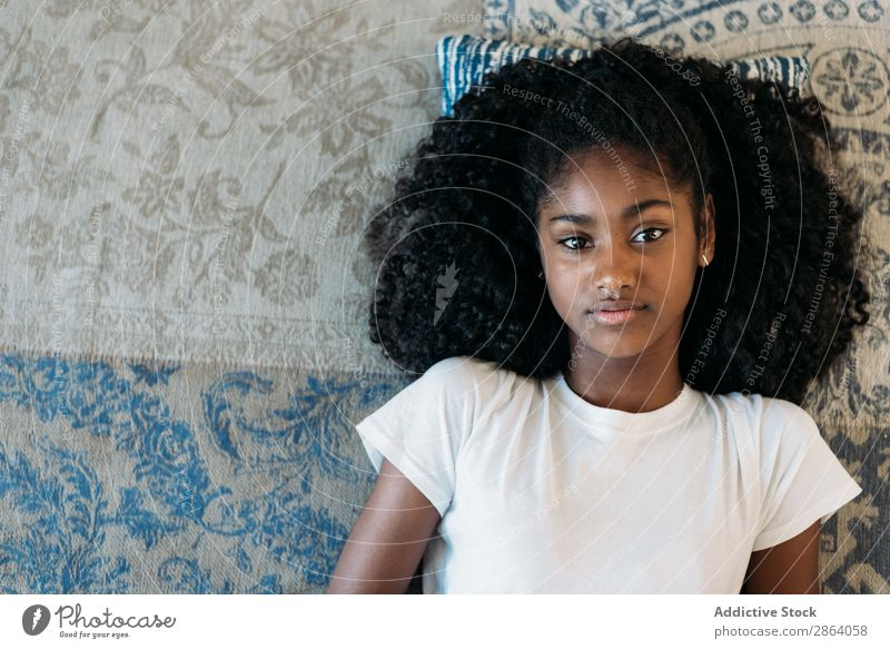 Beautiful young black teenage girl lying down in a rug Girl Youth (Young adults) Ethnic Black Rug Lie Child Caribbean Woman Curly hair African