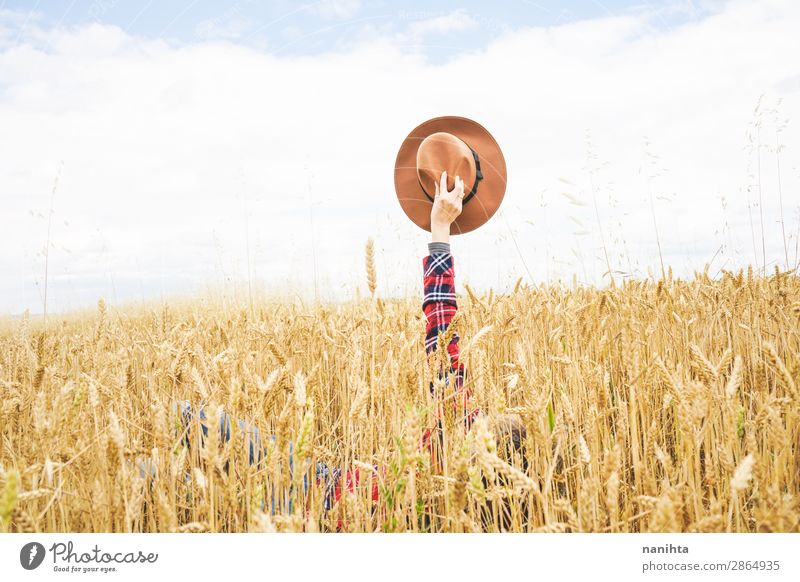Hand holding a cowboy hat over a field of wheat Organic produce Lifestyle Style Design Joy Happy Beautiful Wellness Well-being Contentment Relaxation Freedom