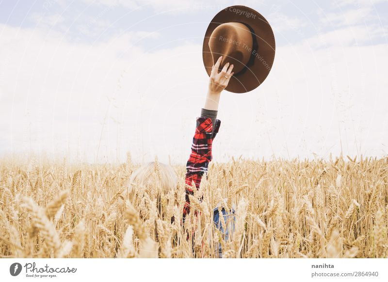 Hand holding a cowboy hat over a field of wheat Organic produce Lifestyle Happy Beautiful Wellness Contentment Relaxation Freedom Summer Agriculture Forestry