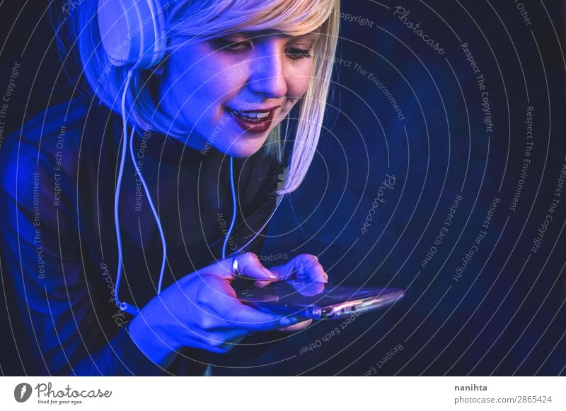 Young woman listening to music Lifestyle Beautiful Face Night life Music Disc jockey Telephone Cellphone Headset Technology Entertainment electronics