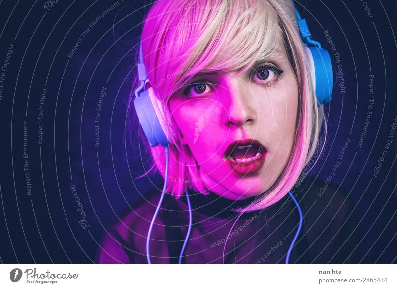 Young woman listening to music and illuminated by neon lights Woman Human being Youth (Young adults) Blue Colour Beautiful 18 - 30 years Face Lifestyle Adults