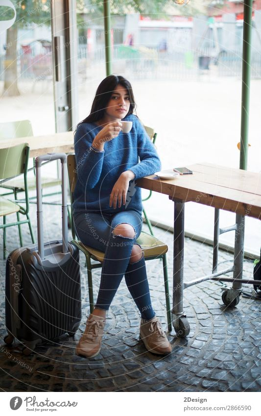 Beautiful young woman sitting while drinking a coffee in a cafe Drinking Coffee Tea Lifestyle Style Relaxation Vacation & Travel Trip Work and employment
