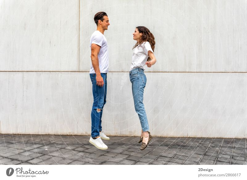 Side view Happy couple in love jumping against grey wall. Woman Human being Youth (Young adults) Man Young woman Young man House (Residential Structure) Joy