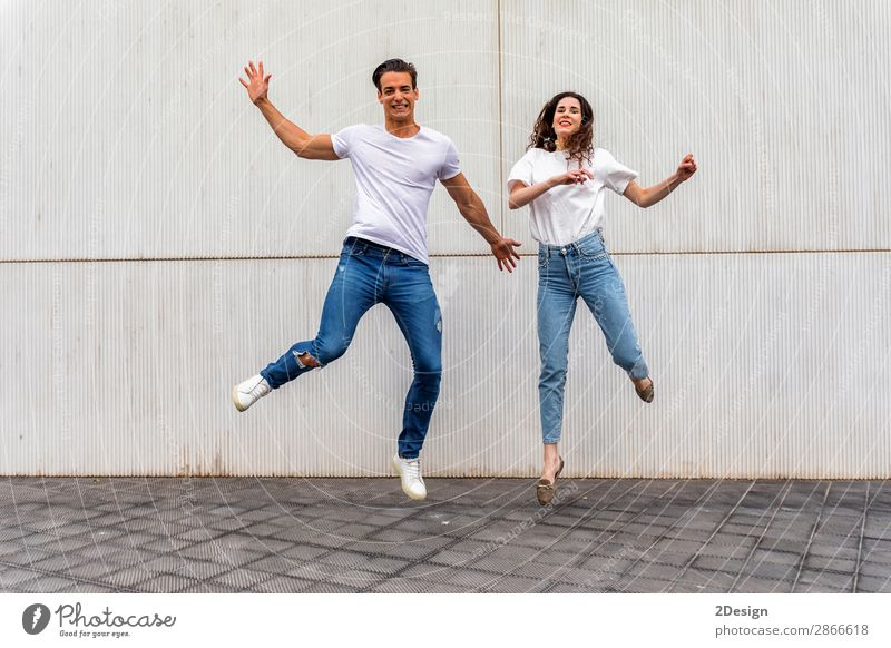 Happy couple in love jumping against grey wall. Woman Human being Youth (Young adults) Man Young woman Young man House (Residential Structure) Joy 18 - 30 years