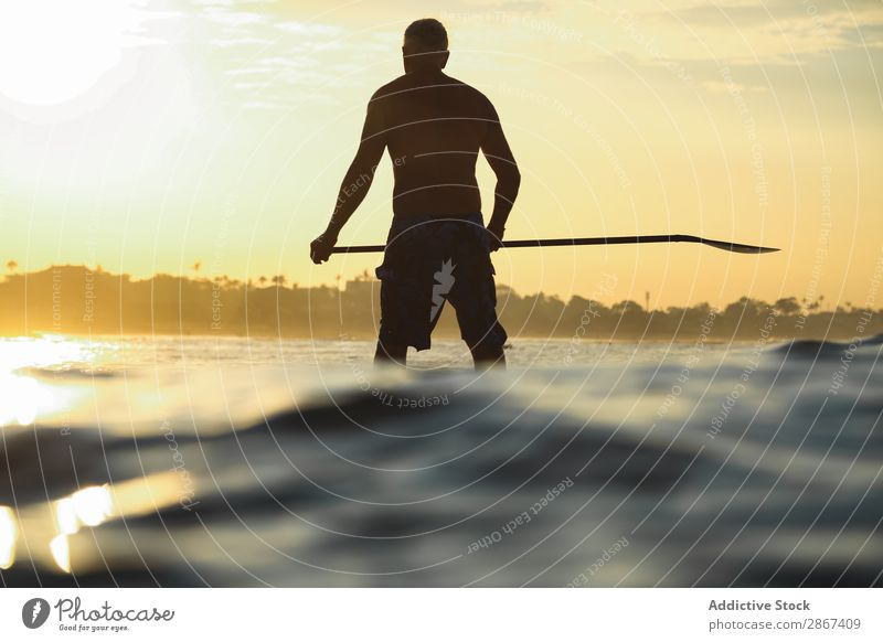 Man with paddle on surf board between waving water at sunset Surfboard Water Surface Sports Bali Indonesia Paddle