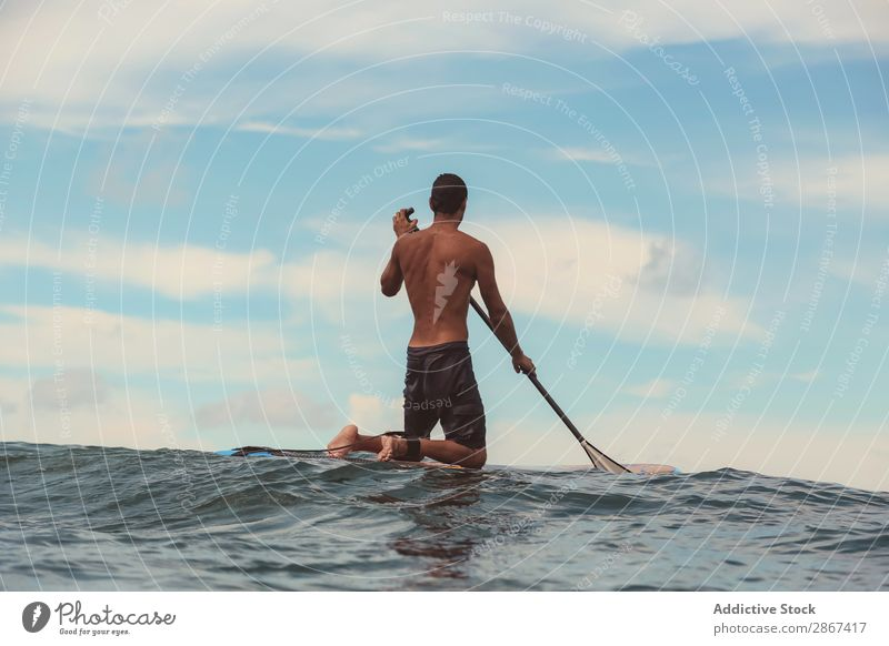 Man with paddle on surf board waving on water Surfboard Water Surface Sports Bali Indonesia Paddle