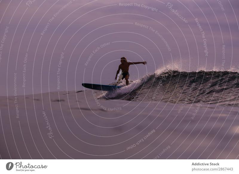 Man on surf board on waving water at sunset Surfboard Water Surface Sports Bali Indonesia Splash