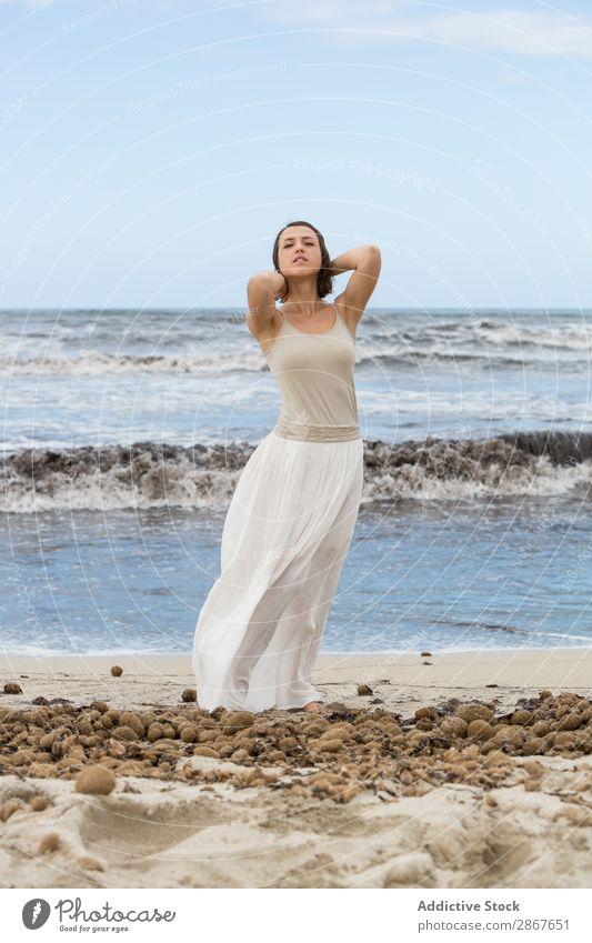 Charming young woman on shore near water Woman Water Coast Ocean Beach Lady waving Posture Youth (Young adults) Thin Attractive Vacation & Travel Passion