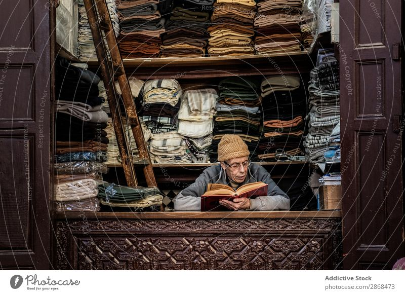 Seller reading book at workplace seller Cloth Markets Book Reading Novel Education Interest Clothing Multicoloured local Shopping Vacation & Travel