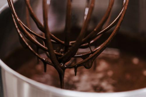 Chocolate immersed whisk close up view Dessert Kitchen Tool Metal Steel Drop Dirty White blend wire Single Syrup background shaker Beater Shake equipment