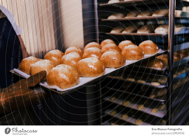 woman holding rack of rolls in a bakery. Bread Happy Kitchen Restaurant School Work and employment Profession Camera Feminine Woman Adults Hand 1 Human being