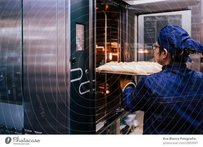 woman holding rack of rolls in a bakery. Bread Happy Kitchen Restaurant School Work and employment Profession Camera Feminine Woman Adults 1 Human being