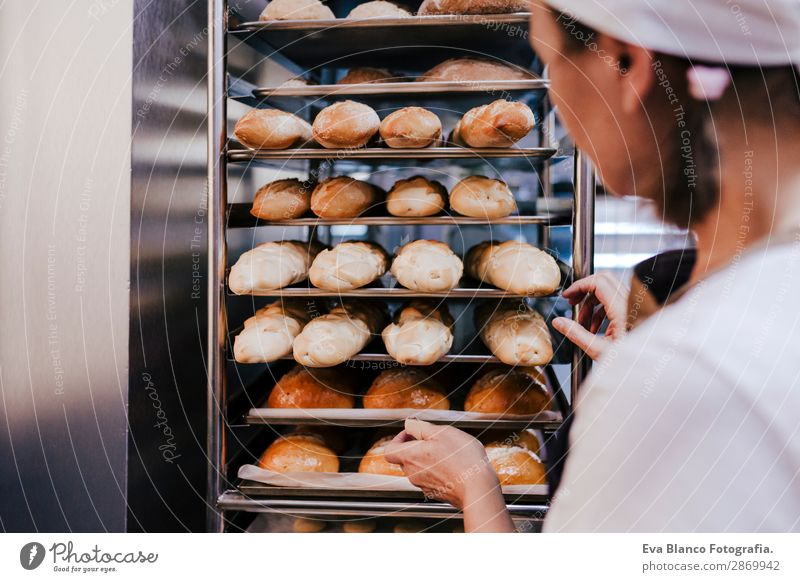 woman holding rack of rolls in a bakery. Bread Happy Kitchen Restaurant School Work and employment Profession Camera Feminine Woman Adults Hand Building