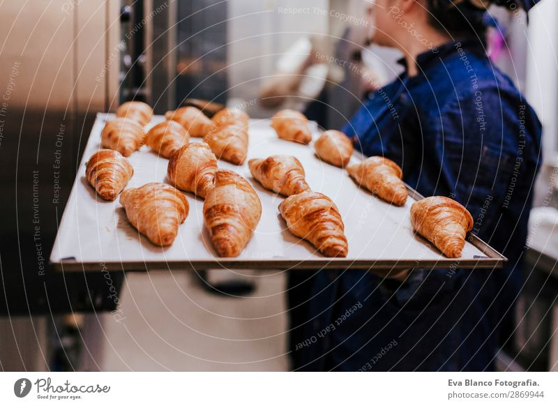 woman holding holding rack of croissants in a bakery Bread Happy Kitchen Restaurant School Work and employment Profession Camera Feminine Woman Adults 1