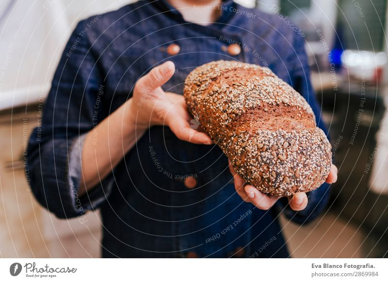 chef in bakery holding seed bread. daytime Bread Nutrition Shopping Healthy Work and employment Profession Business Human being Feminine Woman Adults Hand 1