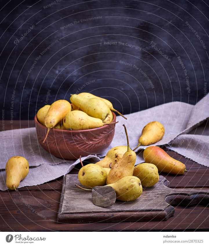 ripe yellow pears in a brown clay bowl Fruit Nutrition Vegetarian diet Diet Bowl Table Nature Autumn Wood Old Eating Fresh Delicious Natural Above Juicy Brown