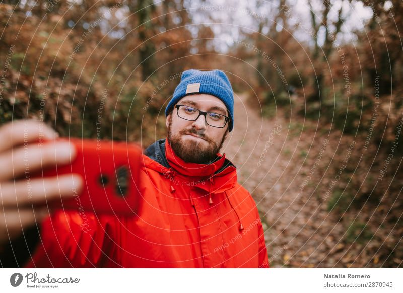 Young man takes a picture in the forest Lifestyle Happy Leisure and hobbies Vacation & Travel Adventure Freedom Hiking Telephone Cellphone PDA Technology