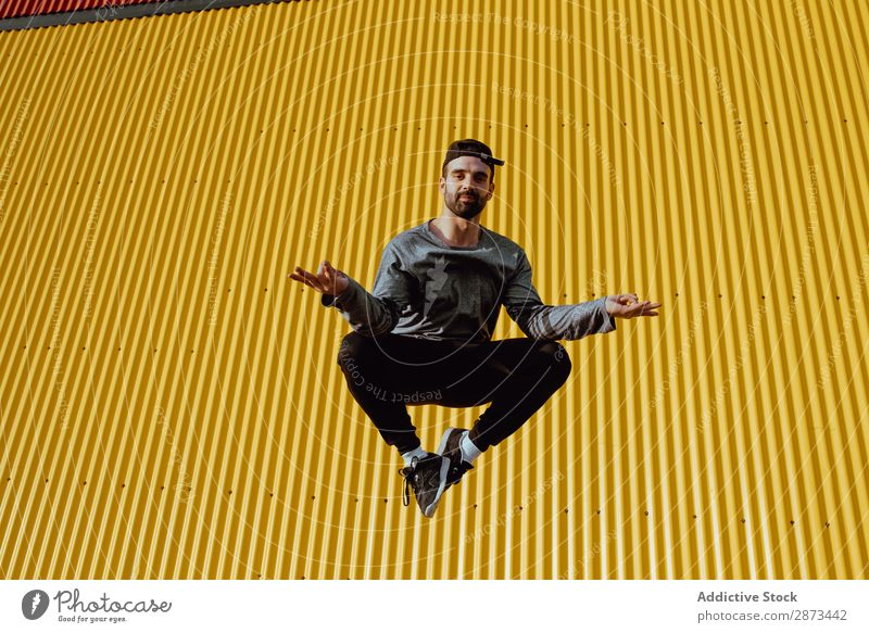 Man jumping near yellow wall Street Jump Wall (building) Yellow Building Stunt Style Easygoing Hip & trendy Fitness Action City Lifestyle Leisure and hobbies