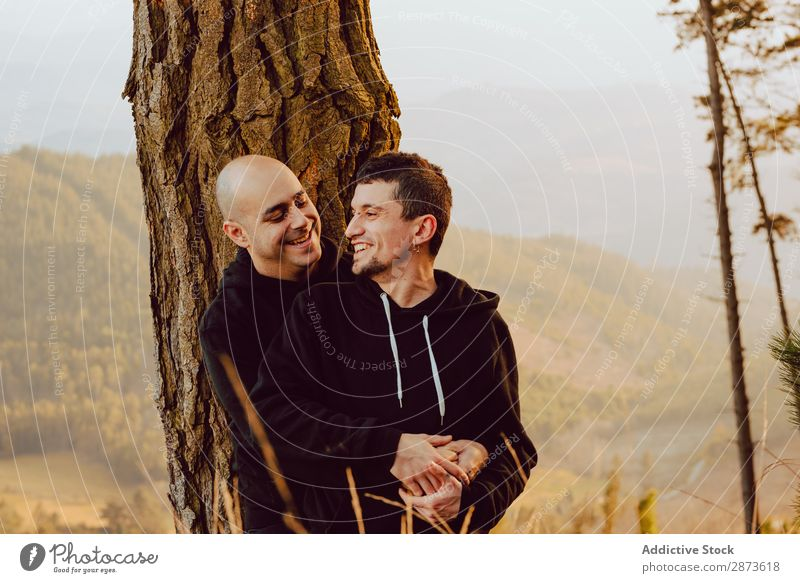 Smiling men hugging near tree in forest on hill Homosexual Couple Embrace Tree Hill Forest Love embracing Valley Picturesque Vantage point romantic Mountain